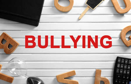 Office stationery and word BULLYING on wooden background, top view Stock Photo