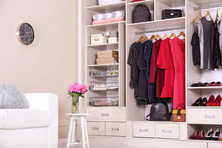 Modern wardrobe with stylish clothes in room interior 免版税图像
