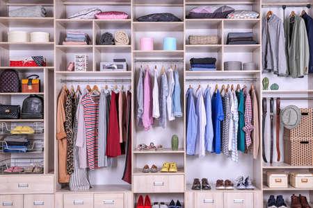 Armario grande con ropa, cosas para el hogar y zapatos diferentes.