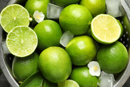 Colander with fresh ripe limes and ice cubes, closeup