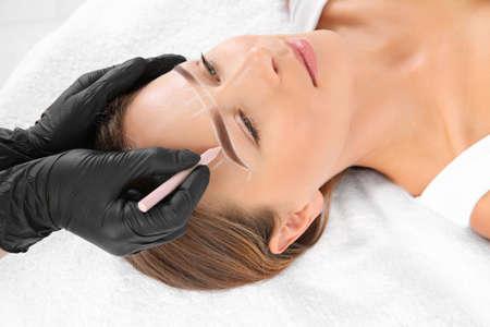 Jonge vrouw ondergaan wenkbrauwcorrectieprocedure in salon Stockfoto