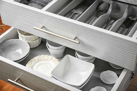 Keramisch serviesgoed en bestek in keukenladen Stockfoto