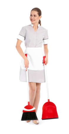 Young chambermaid with broom and dustpan on white background Stock Photo