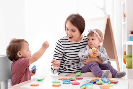 Young nanny playing with cute little children at table, indoors
