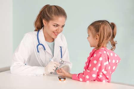 Medico che preleva il campione di sangue della ragazza diabetica utilizzando la penna lancetta in ospedale Archivio Fotografico
