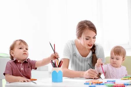 Lindos niños pequeños dibujando con niñera joven, en el interior