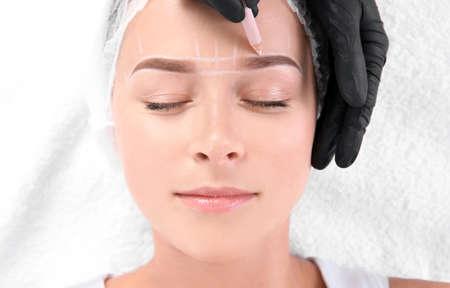 Jonge vrouw ondergaan wenkbrauwcorrectieprocedure in salon, bovenaanzicht