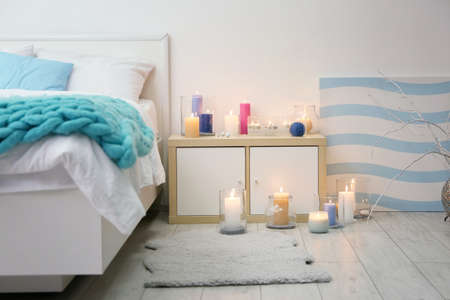 Cozy bedroom decorated with burning candles 免版税图像 - 105728597