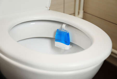 Toilet with rim block in bathroom. Air freshener
