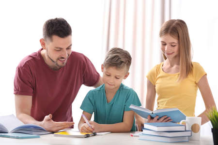 Brother and sister doing homework with father Stock Photo