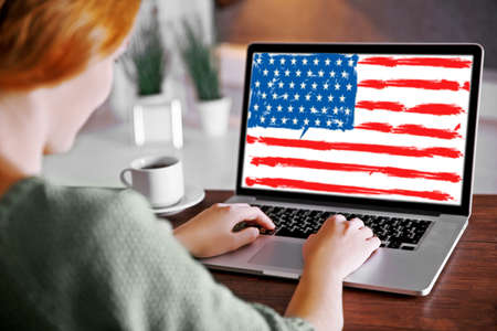 Young woman using laptop with American flag on screen at table