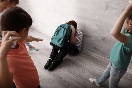 Children bullying little boy with backpack indoors Stock Photo