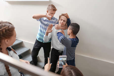Teenagers bullying their classmate at school Stock Photo