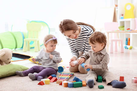 Young nanny playing with little children, indoors Stock Photo