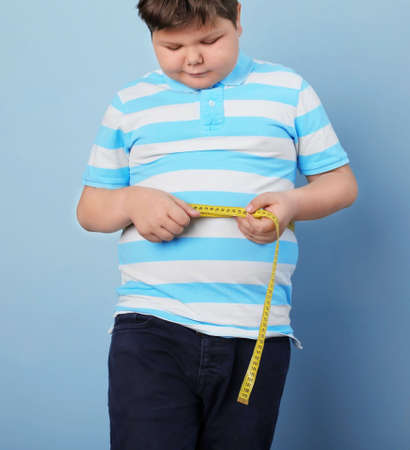 Overweight boy with measuring tape and doctor indoors