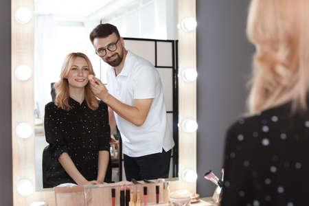 Profesjonalna wizażystka pracująca z klientem w garderobie Zdjęcie Seryjne