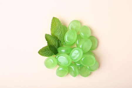 Tasty mint candies and leaves on color background, top view