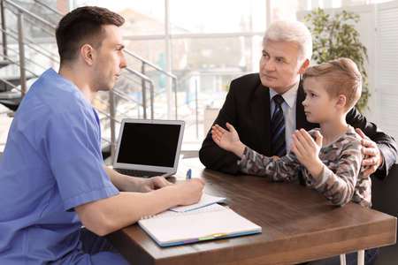 Senior man with his grandson having appointment at child psychologist office Stock Photo