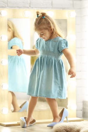 Cute little girl wearing high heeled shoes at home