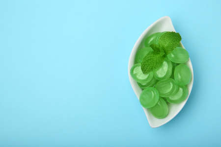 Plate with tasty mint candies and leaves on color background, top view