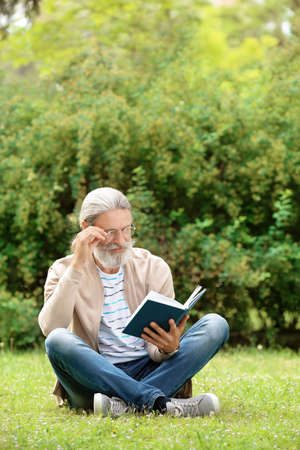 Handsome mature man reading book on green grass in park