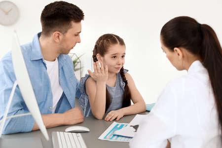 Jonge man met zijn dochter met een afspraak bij het kantoor van de kinderpsycholoog