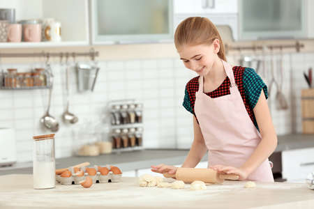 Teenager-Mädchen, das Teig auf Tisch in der Küche rollt Standard-Bild