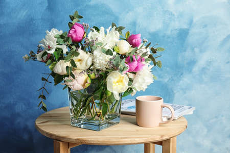 Vase with bouquet of beautiful flowers and cup on table