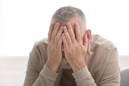 Senior man in state of depression indoors Stock Photo