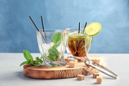 Gläser mit köstlichem Minz-Julep-Cocktail und Eis auf Holzbrett