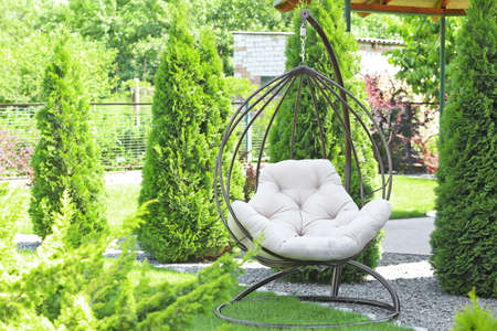 Beautiful English style garden with comfortable hanging chair on sunny day