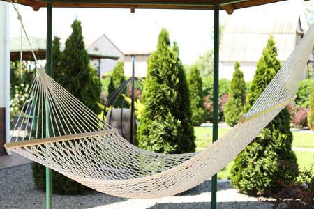 Beautiful English style garden with comfortable hammock on sunny day Stock Photo