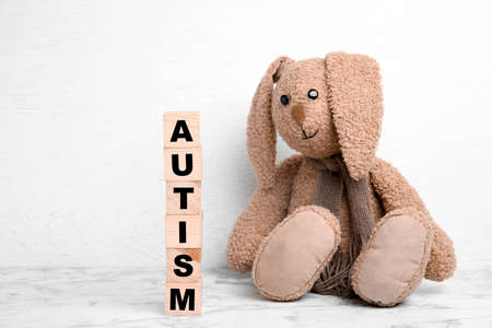 Toy bunny and wooden cubes with word AUTISM on table against light background