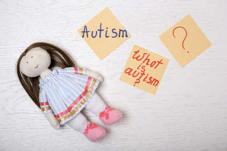 Notes with words related to autism and doll on light background, top view