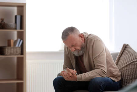 Depressed senior man sitting on sofa indoors