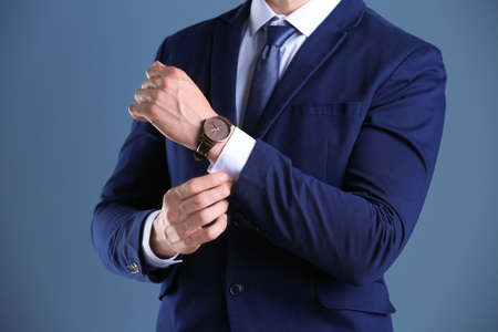 Businessman with wristwatch on color background. Time concept