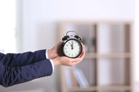 Businesswoman holding alarm clock on blurred background. Time concept Stock Photo