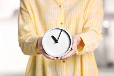 Young woman holding alarm clock on blurred background. Time concept Stock Photo