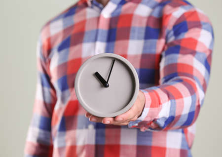 Young man holding alarm clock on grey background. Time concept