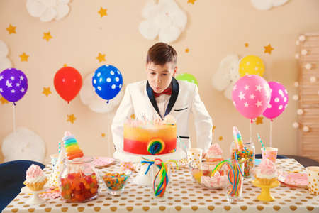 Cute little boy blowing out candles on his birthday cake indoors