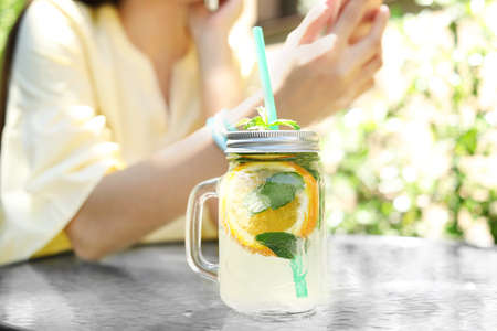 Mason jar with tasty lemonade on table and young woman at cafe, outdoors. Natural detox drink Stock Photo