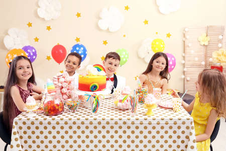 Cute children celebrating birthday at table indoors