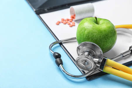 Composition with stethoscope, clipboard, pills and apple on color background. Medical equipment
