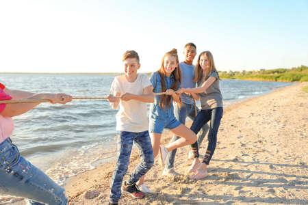 Groupe d'enfants tirant sur la corde pendant un jeu de tir à la corde sur la plage. Camp d'été Banque d'images