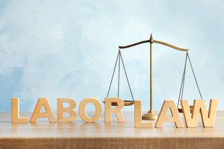 Words LABOR LAW and scales of justice on table against color background Foto de archivo - 105838868