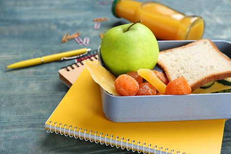 Lunch box with appetizing food and stationery on table