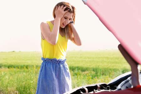 Vrouw stond in de buurt van kapotte auto op platteland benadrukt Stockfoto
