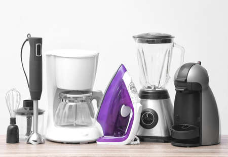Household and kitchen appliances on table against light background. Interior element