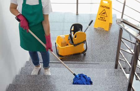Mujer joven, con, trapeador, limpieza, escaleras Foto de archivo