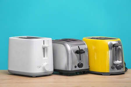 Different toasters on table against color background. Interior element